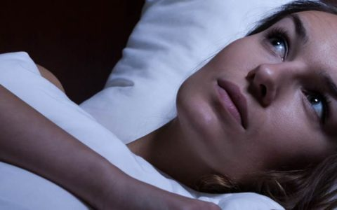 woman lying awake wondering why her heart is racing at night